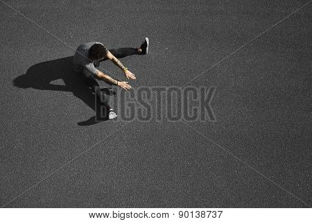 Top view jogging man taking a break during training outdoors in on black asphalt on top view.