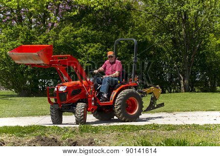 Older Farmer Plowing His Garden With A Compact 4x4 Tractor