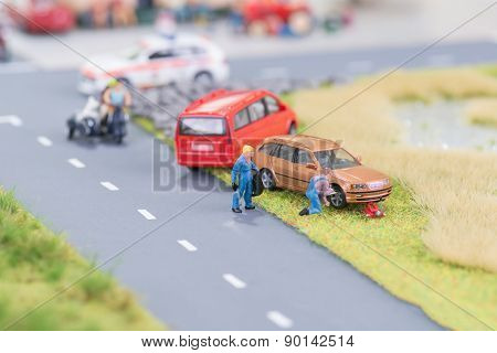 Miniature Mechanics Replacing A Tyre Off The Roadway