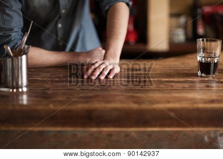 Barman Leaning On Wooden Bar Counter