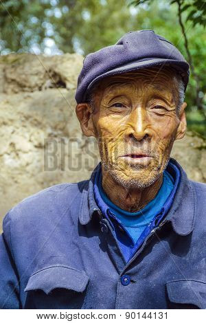 Old Farmer In Traditional Blue Working Class Uniform