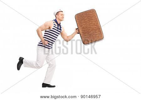 Full length portrait of a young man in a sailor clothes, holding a brown bag and running isolated on white background