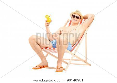 Relaxed young guy drinking a refreshing cocktail seated in a sun lounger chair isolated on white background
