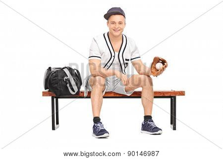 Young sportsman with a baseball glove, sitting on a wooden bench with a sports bag beside him and holding a baseball isolated on white background