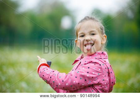 Little Girl Making Faces And Showing Her Tongue
