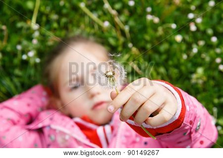 Girl Lying In Grass, Surrounded By Dandelion