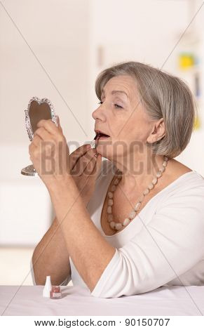 older woman at home looking in the mirror