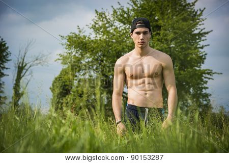 Handsome shirtless fit young man at countryside,