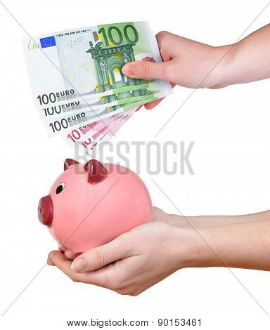 Woman hands holding a pink piggy bank and euro banknotes