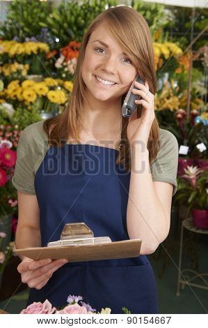 Florist In Shop Holding Clipboard Taking Phone Order
