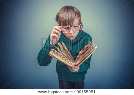 European-looking boy of ten years in glasses reading a book on a