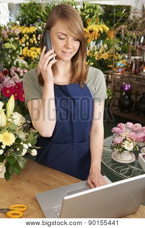 Florist On Phone Using Laptop In Shop