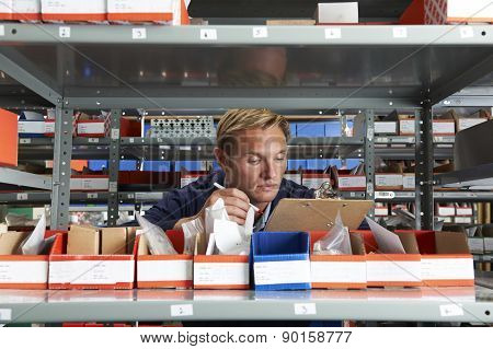 Factory Worker In Store Room Checking Stock
