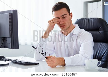 Young Tired Businessman Rubbing His Eye