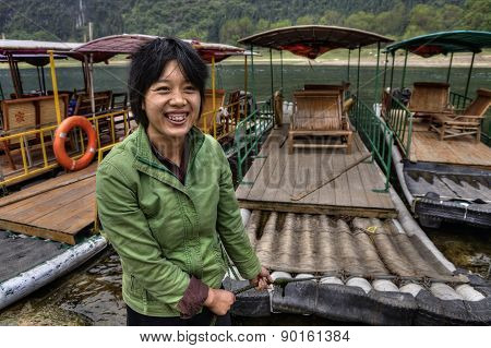 Asian girl ferryman moors bamboo raft, and smiles, Guangxi, China.