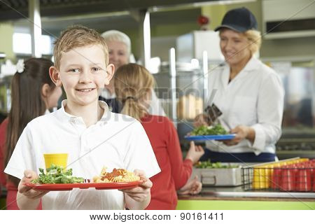 Male Pupil With Healthy Lunch In School Cafeteria