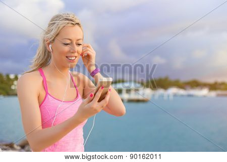 Happy fit woman listening to music during workout outdoors