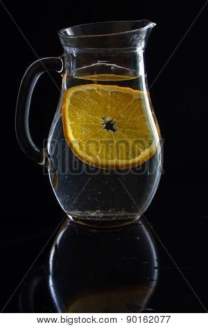Jug With Water And One Slice Of Orange On Black Background