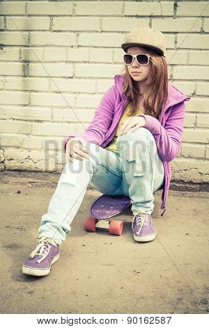 Teenage Girl In Cap And Sunglasses Sits On Skateboard