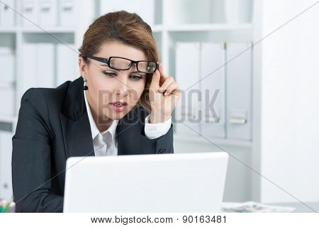 Young Business Woman Looking Intently At Laptop