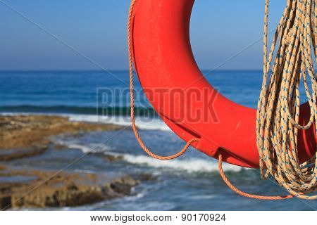 Lifebuoy And Rope Close-up On A Background Of The Rocky Coast