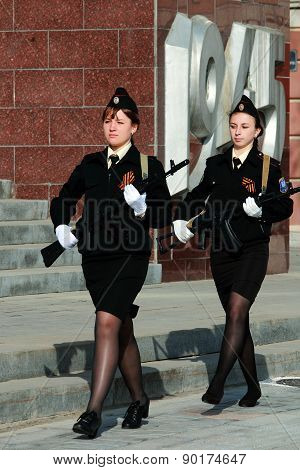 two young women marching with guns