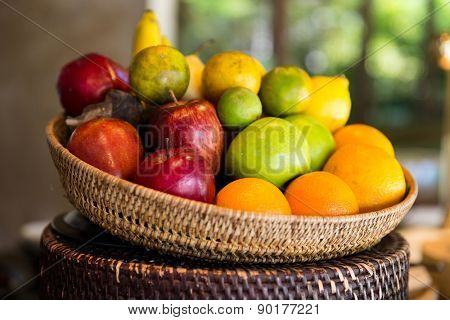 cooking, kitchen, vegetarian and food concept - basket of of fresh ripe juicy fruits at kitchen or home