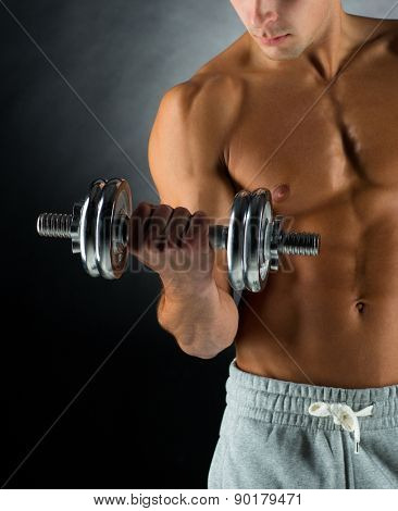 sport, bodybuilding, training and people concept - close up of young man with dumbbell flexing muscles over gray background