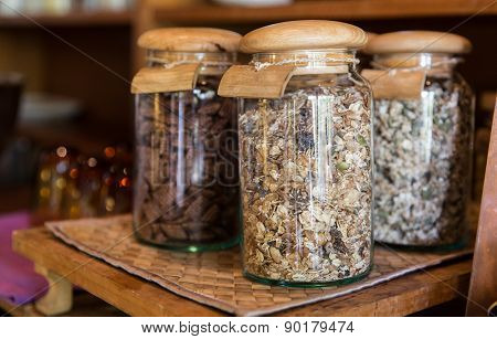 food, storage and eating concept - close up of jars with granola at grocery store