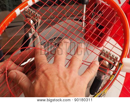 Racquet stringer weaving cross strings in a Tennis racquet