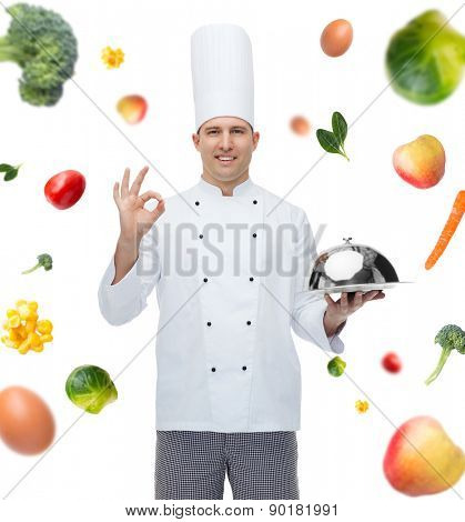 cooking, profession, gesture, vegetarian diet and people concept - happy male chef cook holding cloche and showing ok sign over falling vegetables background