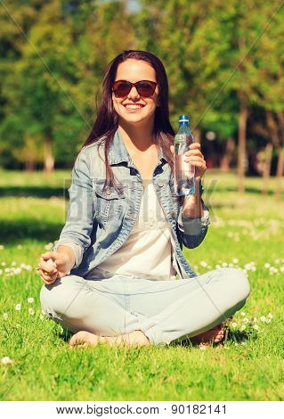 lifestyle, summer, vacation, drinks and people concept - smiling young girl in sunglasses with bottle of water sitting on grass in park