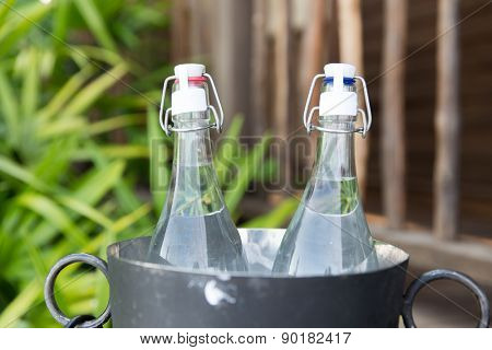 drinks, thirst, refreshment and summer resort concept - couple of water bottles in ice bucket at hotel