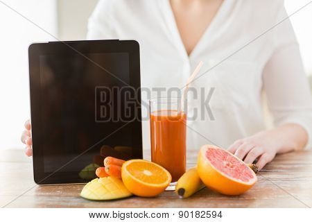 healthy eating, technology, diet and people concept - close up of woman hands with tablet pc, fruits and fresh juice sitting at table