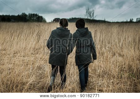Two girls walking across the field in a thunderstorm
