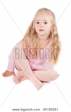 Ballerina in pink dress sitting on the floor