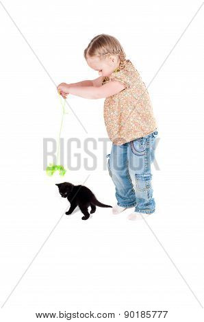 Happy kid girl playing with black cat kitten