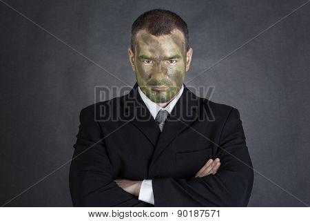 Serious Businessman With Jungle Camouflage Paint And Crossed Arms