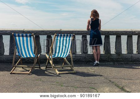 Woman Admiring The Sea From Promenade With Deck Chairs