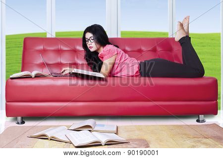 Female Student On Sofa With Laptop And Book