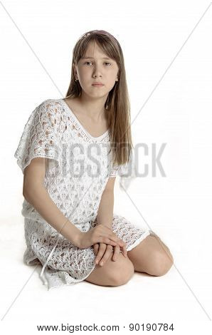 Beautiful slim girl in a white transparent dress on a white