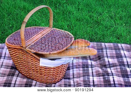 Picnic Basket With Two French Baguette On The Blanket