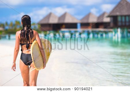 Happy young surf woman at the beach with a surfboard
