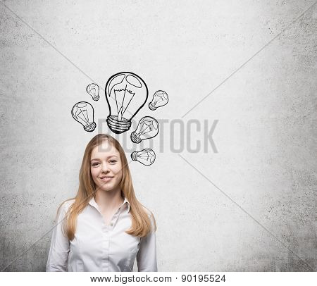 Smiling Young Beautiful Business Lady Is Thinking About New Innovative Ideas. Light Bulbs Are Drawn
