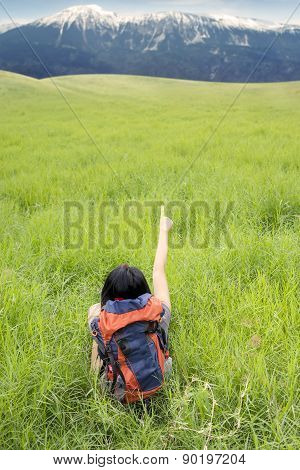 Woman With Rucksack Sitting On Grass