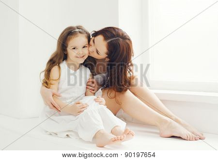 Loving Mother Kissing Daughter At Home In White Room Near Window