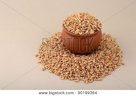 Wheat grains in clay pot with heap