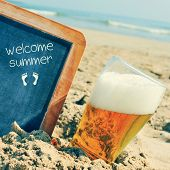 foto of refreshing  - closeup of a glass of refreshing beer and a chalkboard with a wooden frame and the text welcome summer written in it - JPG