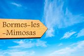 stock photo of mimosa  - Wooden arrow sign pointing destination Bormes - JPG
