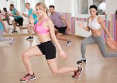 stock photo of squatting  - Fitness group doing squats at the gym - JPG